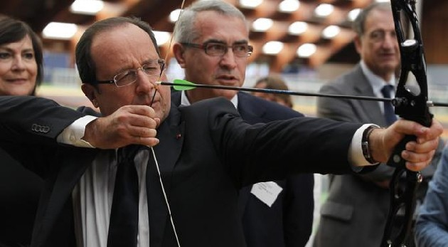 France's President Hollande prepares to shoot an arrow during a visit to meet members of France's 2012 London Olympics team at the training headquarters of INSEP in Paris